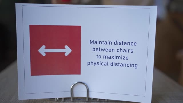 sign on a coffee table with a message about rule of social distancing and six feet apart as an obligation between tables - wet wipe stock videos & royalty-free footage