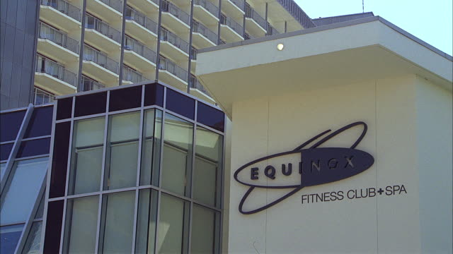 vidéos et rushes de a sign on a wing of a high-rise building identifies the equinox fitness club and spa in los angeles. - architecture