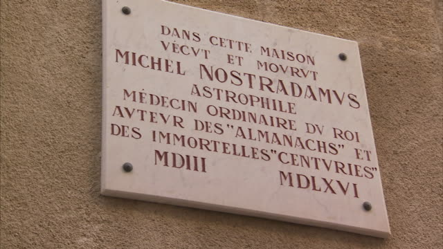 a sign on an exterior wall identifies the house of nostradamus in france. - roman numeral stock videos & royalty-free footage