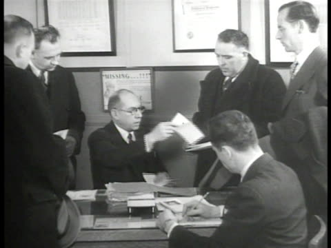 sign on door captain bureau of missing persons captain john stein in office seated at desk handing out information sheets to detectives cu info sheet... - missing persons stock videos & royalty-free footage