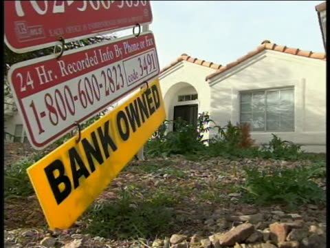 sign on the front lawn of a house says that it is bank owned, meaning foreclosed, and that it is for sale. - 2008 stock videos & royalty-free footage