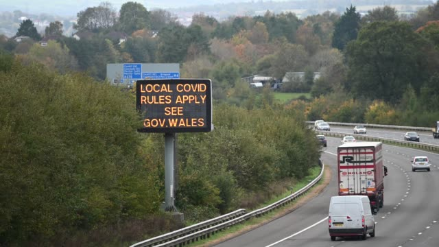 sign on the m4 motorway warns of local covid rules on october 16 in cardiff, wales. the welsh first minister mark drakeford said that people from... - road sign stock videos & royalty-free footage