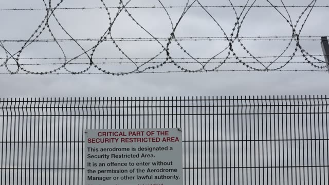 sign on the perimeter fence at manchester airport with an airplane - at the edge of stock videos & royalty-free footage
