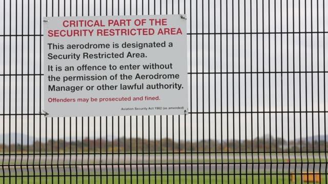 vídeos y material grabado en eventos de stock de sign on the perimeter fence at manchester airport with an airplane - en el borde