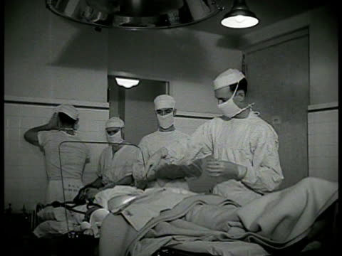 sign 'operating room' int ms doctors preparing patient on operation table ms corpsman watching ms surgeons operating ms patient laying wwii - hospital corpsman点の映像素材/bロール