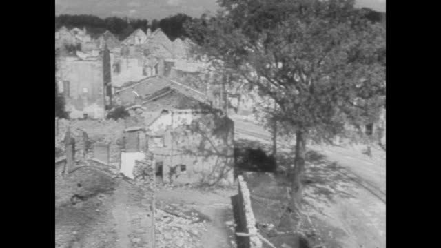 """oradour-sur-glane"" and views of the shattered village / two men walking in the interior of church ruins / a man and his dog in rubble and him... - postwar stock videos & royalty-free footage"