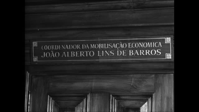 sign over office doors 'jose alberto lins de barros' int ms alberto sitting at desk signing papers paper work wwii economist - 1899 stock videos and b-roll footage
