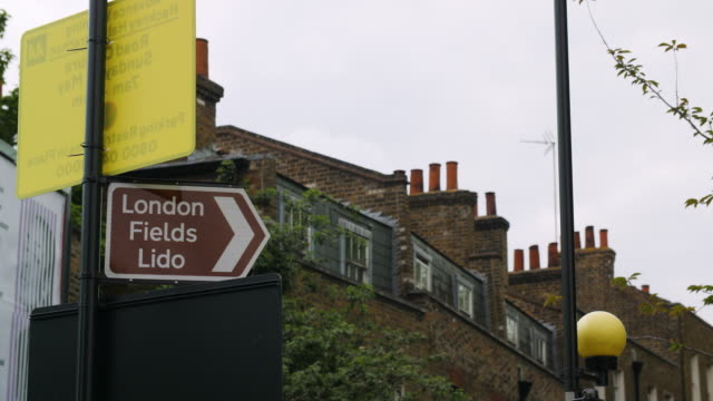 sign pointing to london fields lido with rooftops in background - sign stock videos & royalty-free footage