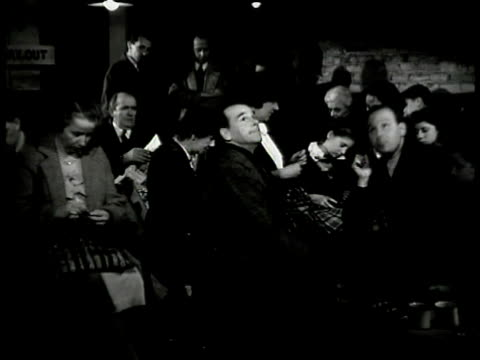 sign 'public air raid shelter' int people sitting huddled closely. man speaking '...the r.a.f. over berlin giving them a dose of their own medicine.'... - 1940 stock videos & royalty-free footage