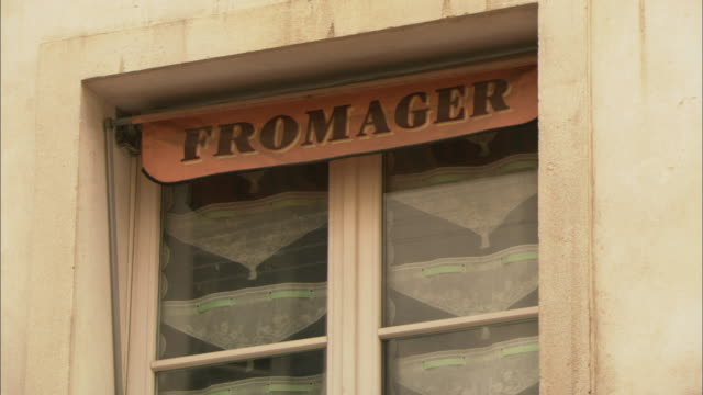 cu la sign reading fromager hanging in window outside cheese shop, paris, france - shop sign stock videos & royalty-free footage