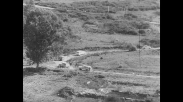 vidéos et rushes de cu sign reading 'frontier ahead' in english arabic and hebrew / un vehicles drive through border gate / israeli troops hold observation points along... - 1967
