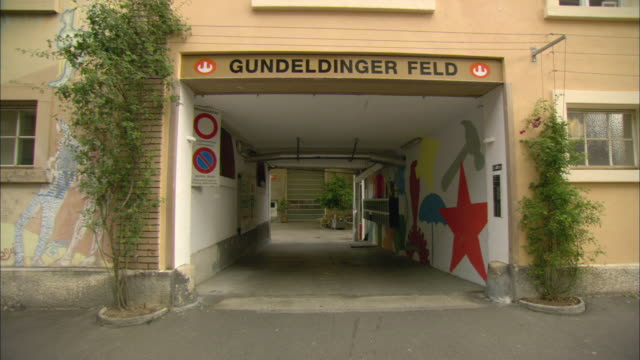 vídeos de stock, filmes e b-roll de ws sign reading gundeldinger feld painted over entryway to building / basel, switzerland - portão