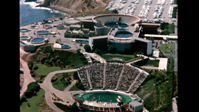sign reading, 'marineland, world's largest oceanarium' / aerial of marineland on cliff's edge / aquariums, amphitheaters and tanks dot the landscape... - palos verdes stock videos & royalty-free footage