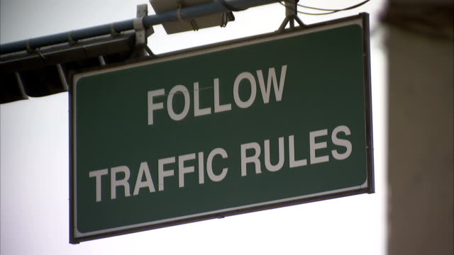 """A sign reads, """"Follow Traffic Rules""""."""