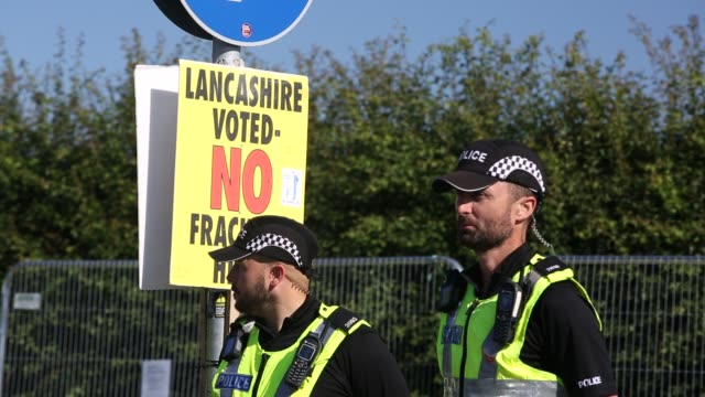 sign reads 'lancashire voted no fracking here.' police guarding cuadrilla's fracking site at preston new road, little plumpton, lancashire, uk on... - oil industry stock videos & royalty-free footage