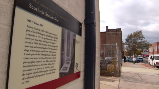 ms sign saying african american heritage trail scurlock studio site is affixed to wall overlooking u street / washington, district of columbia, united states - 英字点の映像素材/bロール
