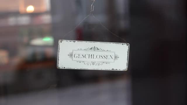 "sign saying ""closed"" stands at the entrance of a cafe in the district charlottenburg-wilmersdorf next to kurfuerstendamm during a four-week... - geschlossen allgemeine beschaffenheit stock-videos und b-roll-filmmaterial"