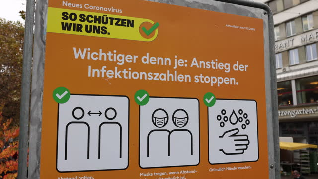 vídeos de stock, filmes e b-roll de sign saying how to behave to avoid a covid-19 infection stands in the city center during the coronavirus pandemic on october 23, 2020 in st. gallen,... - evitar os outros