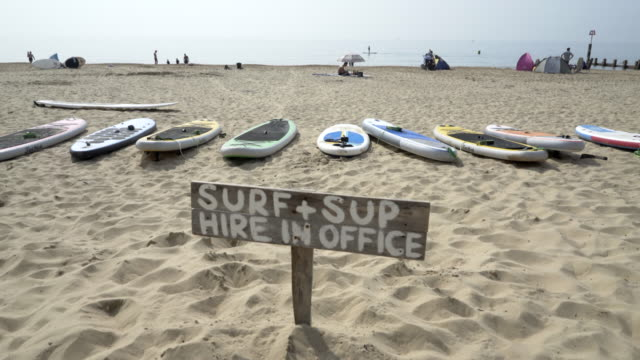 a sign saying surf and sup. - bournemouth stock-videos und b-roll-filmmaterial