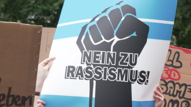"sign says ""no to racism"" at a demonstration with over 10,000 people who protest against racism and police brutality in tribute to george floyd on... - respect stock-videos und b-roll-filmmaterial"