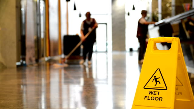 sign showing warning of caution wet floor and workerw cleaning hall floor of  business building. - pavimento video stock e b–roll
