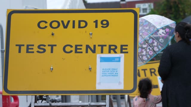 sign shows the way to a covid-19 testing centre in walthamstow as small child waits for a coronavirus covid-19 test on september 23, 2020 in london,... - small stock videos & royalty-free footage
