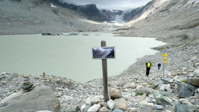 a sign shows where the pasterze glacier reached in 2010 as the glacier in its current state is seen far behind on august 13 2019 near heiligenblut am... - 2010 2019 stock videos & royalty-free footage