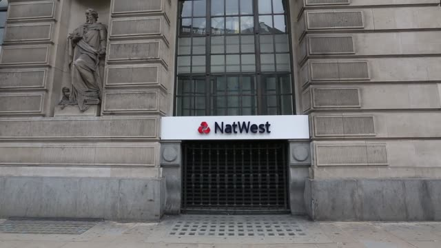 A sign sits on the wall of a NatWest bank branch part of the Royal Bank of Scotland Group Plc in London Side view NatWest sign people and traffic in...
