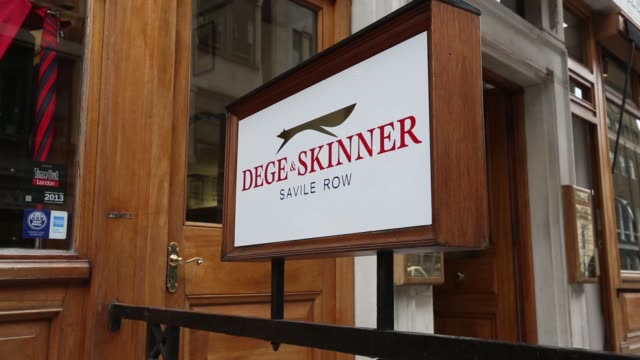 a sign stands outside the entrance to the tailors dege skinner on savile row in london the window display of the tailors dege skinner an employee... - savile row stock videos and b-roll footage