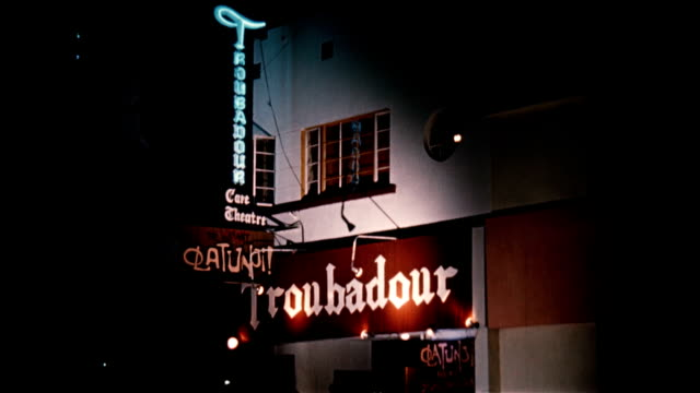 / CU sign that reads 'TROUBADOUR' / CU front of café Troubadour café on January 01 1956 in Hollywood California