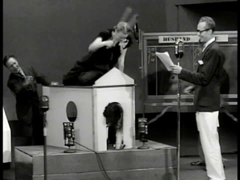 vídeos de stock, filmes e b-roll de sign 'the better half' radio program. contestants on stage w/ audience fg. edmund 'tiny' ruffner naming animals husband in dog house making sounds... - game show