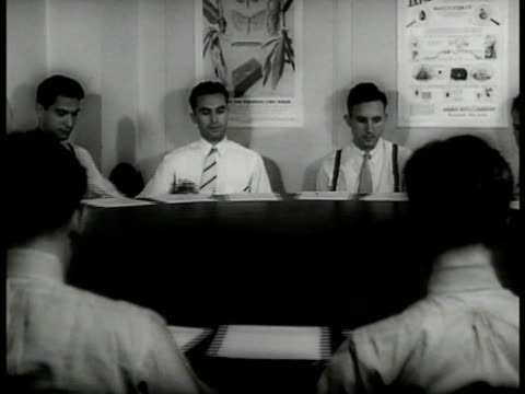 sign 'the european corn borer.' men sitting at revolving table w/ papers. sign 'japanese beetle watch for it.' vs japanese beetles eating fruit corn.... - reportage点の映像素材/bロール