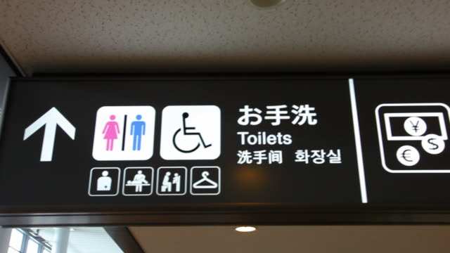 cu pan sign to restroom and currency exchange in english and japanese script / tokyo, japan   - japanese script stock videos & royalty-free footage