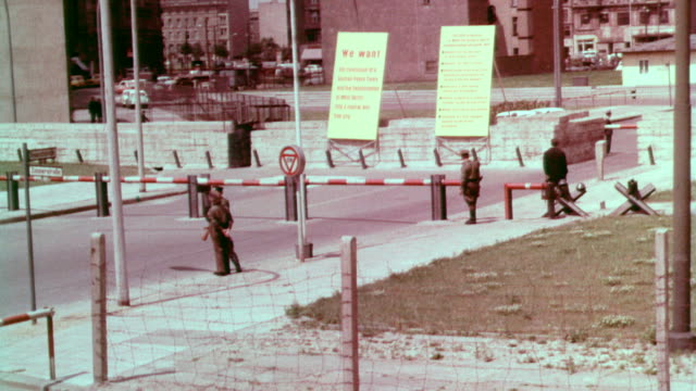vídeos de stock e filmes b-roll de sign 'us army checkpoint charlie' / border crossing area with guards on patrol / looking into the eastern sector of berlin from the friedrichstrasse... - 1963