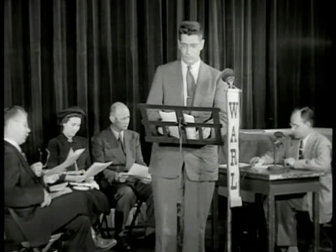 vídeos de stock e filmes b-roll de sign 'warl.' int man at microphone in studio, citizen's committee members seated bg. man behind desk giving signal. man at microphone talking.... - filme documentário