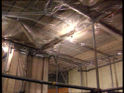 lib england int sign warning that asbestos removal is in progress building with areas shrouded in plastic worker wearing protective clothing up... - asbest stock-videos und b-roll-filmmaterial