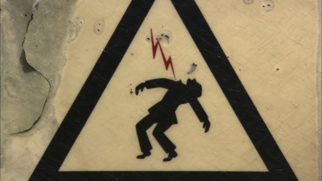 vídeos de stock, filmes e b-roll de a sign warns of death by electrocution at a power plant. - alta voltagem