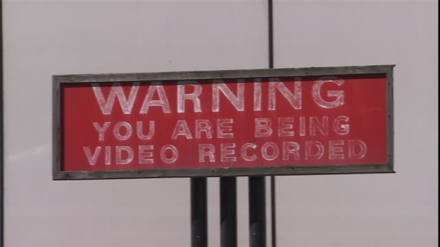 a sign warns of video surveillance. - warning sign stock videos & royalty-free footage