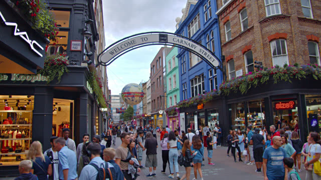 sign welcome to carnaby street. tourists shopping at shopping malls and retail stores. walkway. - tourist stock videos & royalty-free footage