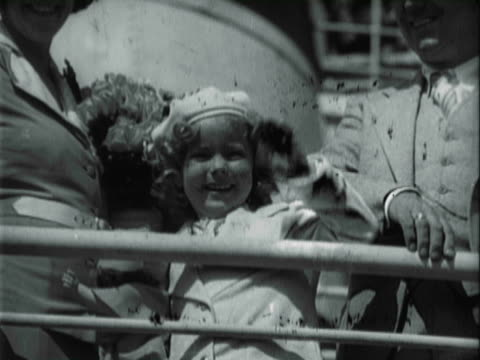 Whoopee for Fort Worth Frontier / Child star Shirley Temple wearing jacket and matching beret standing on deck of boat holding a doll smiling and...