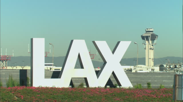 MS, 'LAX' sign with air traffic control tower and jet taxiing in background, Los Angeles, California, USA