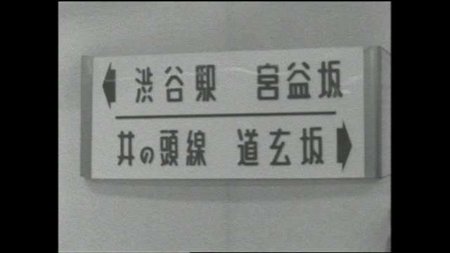 stockvideo's en b-roll-footage met a sign with japanese characters on it guides shoppers through an underground shopping center. - shibuya shibuya station