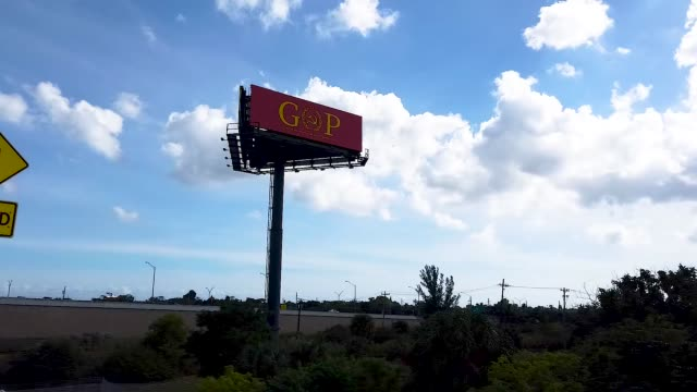 """A sign with the words """"GOP"""" and the """"O"""" fashioned in the shape of a hammer and sickle topped by a star which mimics the former Soviet Union's flag is..."""