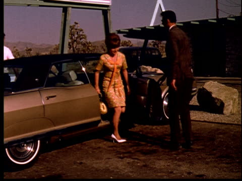 1965 FILM MONTAGE LA WS sign Yucca Valley Ranchos Land & Development/ TD Man opening car door for wife/ couple following man into real estate office/ Yucca Valley, California