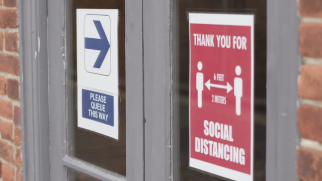 covid-19 signage about social distancing at small business during corona pandemic, life after lockdown new normal - entrance sign stock videos & royalty-free footage