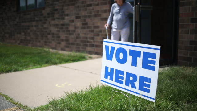 Signage and voters during the Iowa primary election in Davenport Iowa US on Tuesday June 5 2018