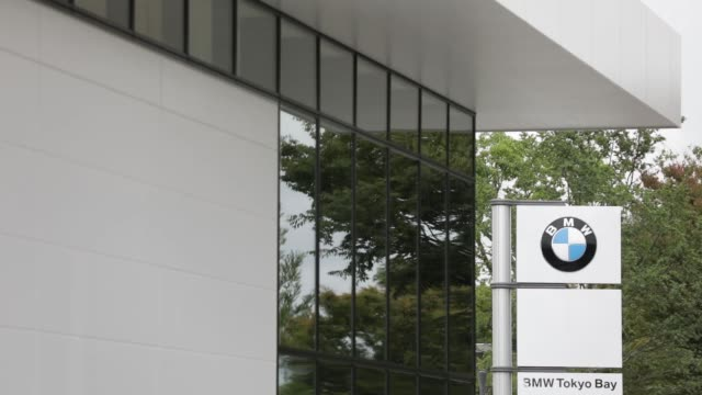 stockvideo's en b-roll-footage met signage for bayerische motoren werke ag stands outside a bmw group tokyo bay showroom in tokyo, japan, on monday, oct. 3 visitors look at a bmw x1... - toonzaal