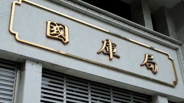 Signage for Department of the Treasury is displayed at the Taiwan Central Bank headquarters building in Taipei Taiwan on Monday Jan 22 Pedestrians...