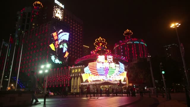 signage for hotel lisboa, operated by sjm holdings ltd, is illuminated at night in macau, china, on tuesday, may 6 pedestrians walk past the casino... - macao stock videos & royalty-free footage