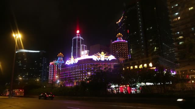 Signage for Hotel Lisboa operated by SJM Holdings Ltd is illuminated at night in Macau China on Tuesday May 6 Pedestrians walk past the Casino Lisboa...